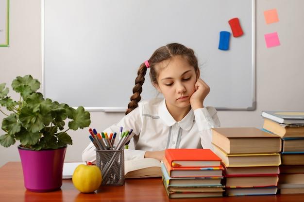 Schulschülerin, die das buch liest und im klassenzimmer sitzt