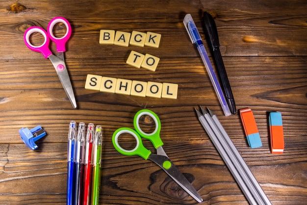 Schulset mit aufschrift zurück zur schule, bleistifte, kugelschreiber, schere, radiergummi auf holzschreibtisch