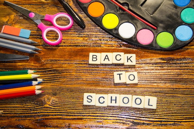 Schulset mit aufschrift zurück zur schule, bleistifte, kugelschreiber, schere, radiergummi und aquarellfarben auf holzschreibtisch