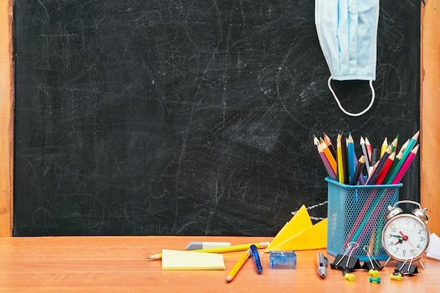 Schulstillleben, schreibwaren auf dem tisch und eine medizinische maske in der schulbehörde, schule, universität, hochschule