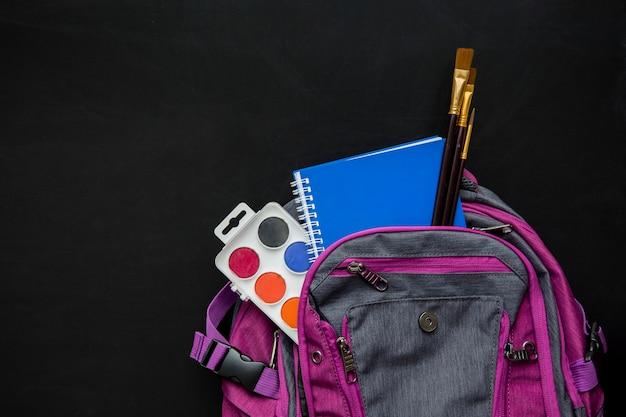 Schultasche mit pinseln, aquarellen und heft