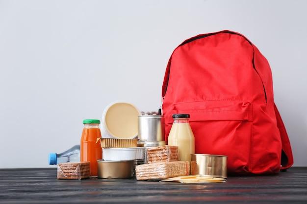 Schultasche mit verschiedenen produkten auf dem tisch. konzept des rucksack-food-programms