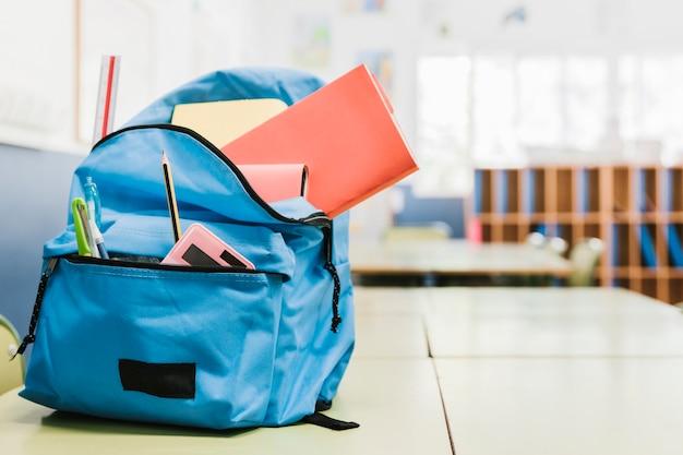 Schultasche mit verschiedenen werkzeugen auf schreibtisch