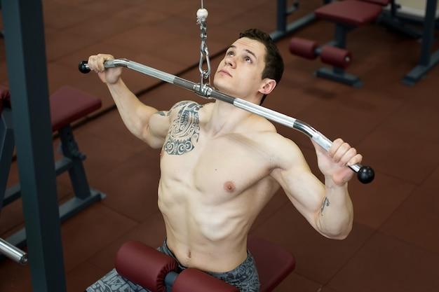 Schulter-pulldown-maschine. fitness-mann, der lat pulldown-training im fitnessstudio ausarbeitet. oberkörperkraftübung für den oberen rücken.