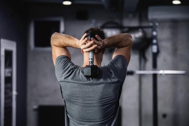 Schulter- und armübungen. hintere aufnahme eines gutaussehenden mannes, der eine hantel zwischen seinen schulterblättern hält und seine arm-, schulter- und rückenmuskulatur in einem modernen sportzentrum stärkt