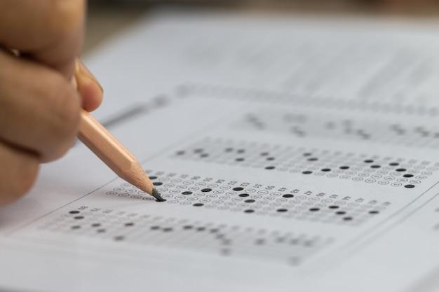 Schultestkonzept für bildungseinrichtungen: hände, die einen bleistift halten, um prüfungen zu testen, die einen antwortbogen oder eine übung schreiben, um die zulassungsprüfung auszufüllen, mehrere kohlepapiercomputer im klassenzimmer der universität