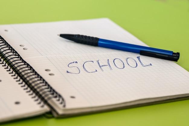 Schultext auf einem notizbuch mit bleistiften geschrieben