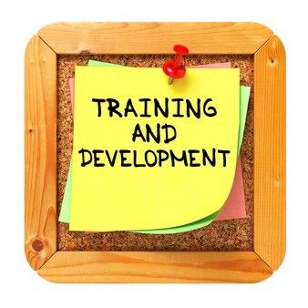 Schulungs- und entwicklungstext auf gelbem aufkleber auf cork bulletin