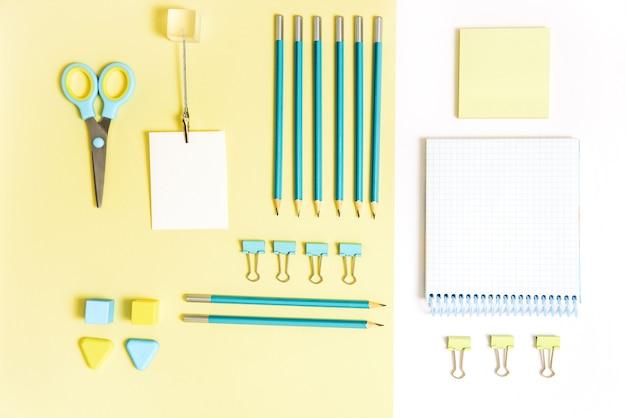 Schulwerkzeuge auf blauem und gelbem hintergrund. top view knolling.back to school, schulbedarf - bleistifte und farben, lineal und radiergummi, büroklammern und scheren, notizblöcke und notizbücher.
