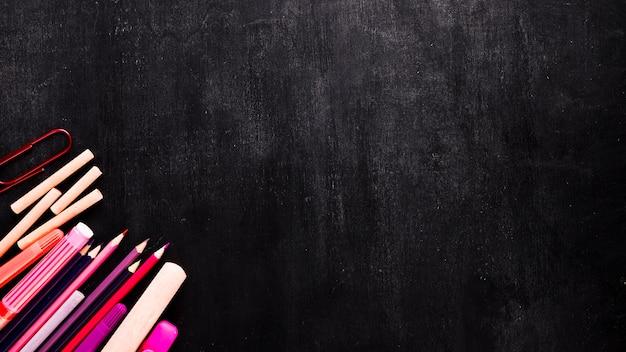 Schulwerkzeuge auf schwarzem schreibtisch