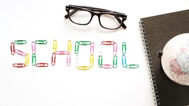 Schulwort gebildet von den büroklammern nahe gewundenem notizblock; globus und brille auf weißer fläche
