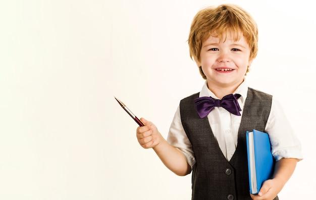 Schulzeit. kinderjunge mit notizblock und stift. schüler. ausbildung. grundschulkind.