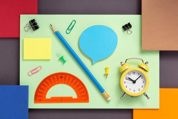 Schulzubehör und bürobedarf auf abstraktem buntem papierhintergrund