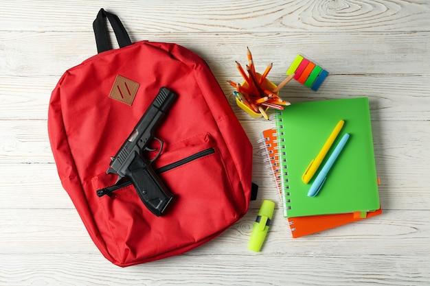 Schulzubehör und pistole auf weißem holztisch. schulgewalt