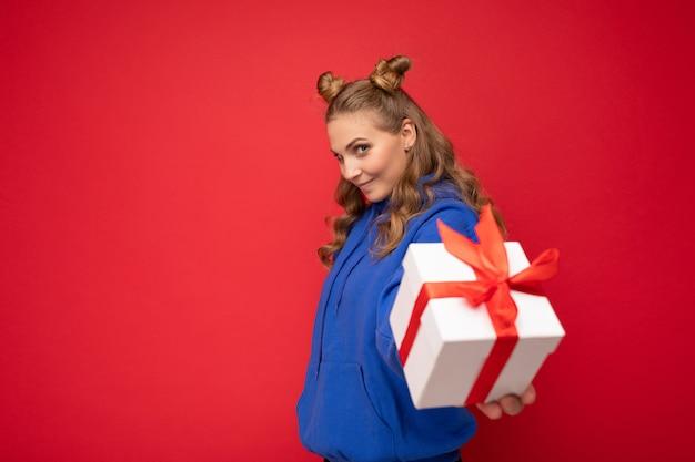 Schuss der attraktiven glücklichen jungen blonden frau lokalisiert über der roten hintergrundwand, die blauen trendigen hoodie hält, der geschenkbox hält und kamera betrachtet. speicherplatz kopieren, modell