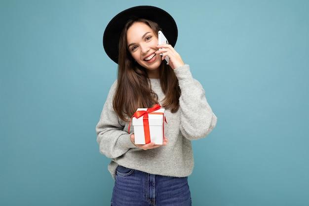 Schuss der attraktiven glücklichen positiven lustigen lustigen jungen brunetfrau lokalisiert über der blauen hintergrundwand, die schwarzen hut und grauen pullover hält, die geschenkbox hält, die auf handy spricht und kamera betrachtet.