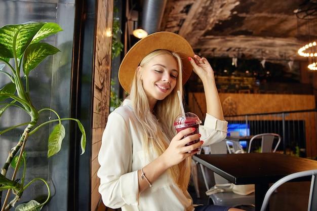 Schuss der attraktiven jungen langhaarigen blonden dame, die in der nähe des fensters im modernen café der stadt sitzt und beerengetränk trinkt, während sie auf ihre bestellung wartet, positiv lächelt und ihren hut mit erhobener hand hält