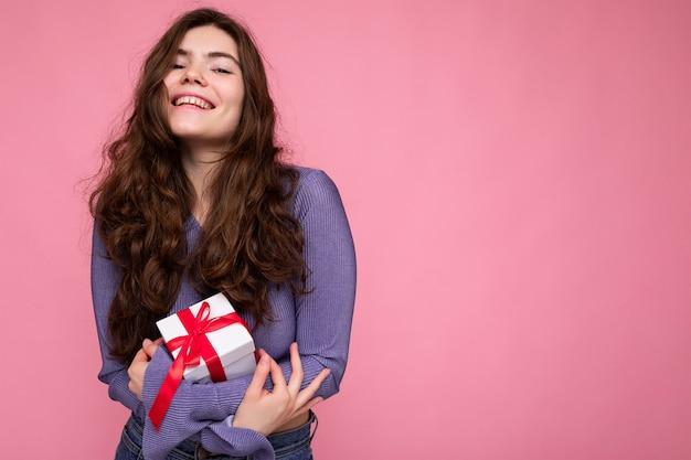 Schuss der attraktiven positiv lächelnden jungen brünetten frau lokalisiert über bunte hintergrundwand, die alltägliches trendiges outfit trägt