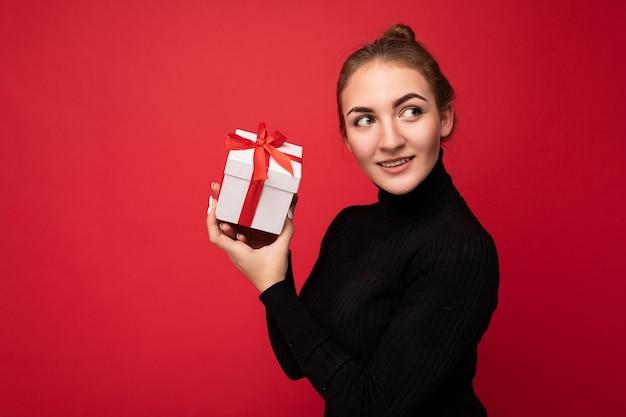 Schuss der attraktiven positiven lächelnden jungen brünetten frau lokalisiert über bunte hintergrundwand, die alltägliches trendiges outfit trägt, das geschenkbox hält und zur seite schaut.