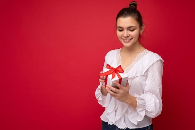 Schuss der bezaubernden glücklichen lächelnden jungen brünetten frau lokalisiert über der roten hintergrundwand, die weiße bluse trägt, die weiße geschenkbox mit rotem band hält und nach unten schaut. speicherplatz kopieren, modell