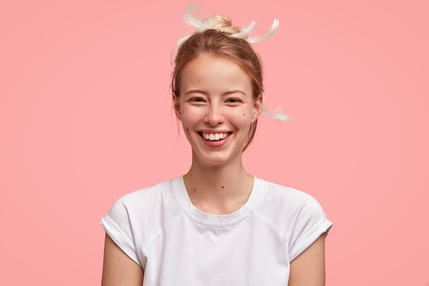 Schuss der glücklichen frau wacht am frühen morgen in guter laune auf, hat ansprechendes aussehen, trägt lässiges t-shirt, isoliert über rosa wand. frohe frau freut sich wochenende genießt langen schlaf und angenehme träume