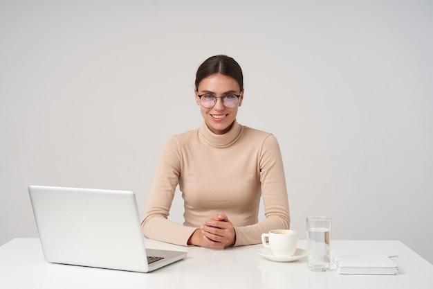 Schuss der jungen fröhlichen schönen brünetten dame, die sich im büro trifft, in guter stimmung ist und angenehm lächelt und hände auf dem tisch hält, während sie über weißer wand sitzt