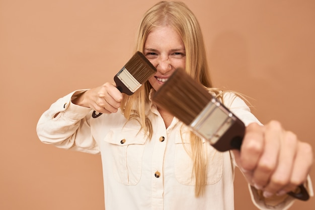 Schuss der jungen hausmalerin in uniform posiert isoliert mit zwei pinseln in ihren händen