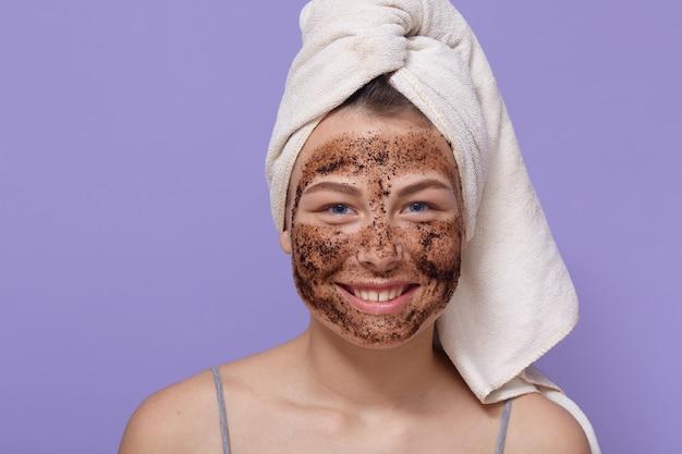 Schuss der jungen lächelnden frau, die braune kosmetische maske auf ihrem gesicht anwendet und ihre haut zu hause reinigt