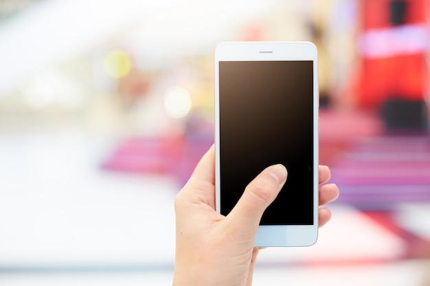 Schuss der nicht wiedererkennbaren frau hält modernes smartphone mit leerem schwarzen bildschirm