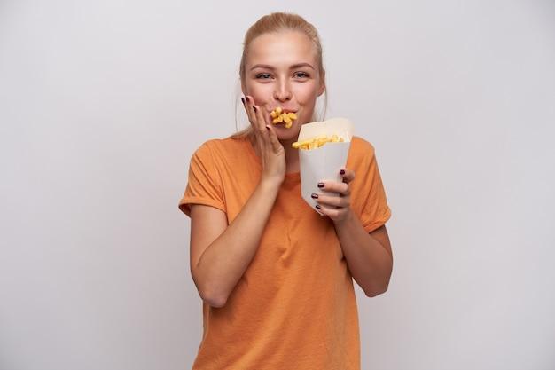 Schuss der positiven jungen hübschen blonden frau mit lässiger frisur, die fröhlich in die kamera mit mund voller pommes frites schaut, hungrig und glücklich ist, mahlzeit zu erhalten, lokalisiert über weißem hintergrund