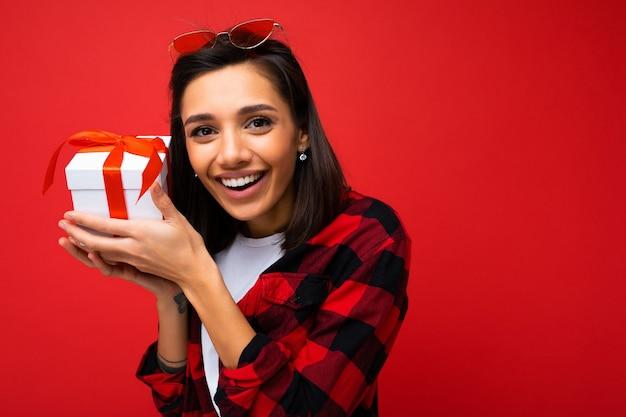 Schuss der positiven lächelnden jungen frau lokalisiert über der roten hintergrundwand, die weiß trägt