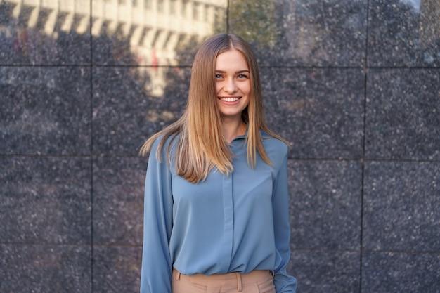 Schuss der schönen jungen geschäftsfrau, die blaues chiffonhemd trägt, während sie steht und auf grauer marmorwand aufwirft