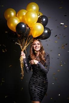 Schuss der smiley-frau, die luftballons hält