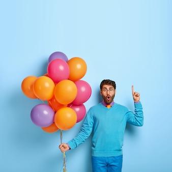 Schuss des betäubten kerls mit luftballons, die im blauen pullover aufwerfen