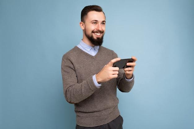Schuss des glücklichen hübschen jungen brünetten unrasierten mannes mit bart, der alltäglichen grauen pullover und blaues hemd trägt
