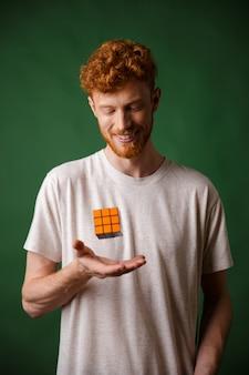 Schuss des jungen lächelnden bärtigen lesekopfmannes, der rubik's cube hält