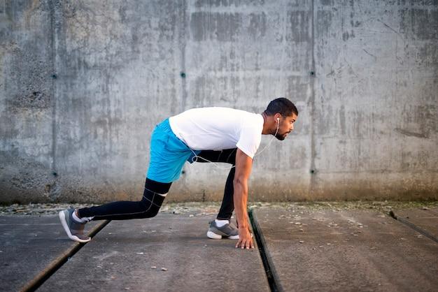 Schuss des jungen sportlichen athleten bereit für den sprint