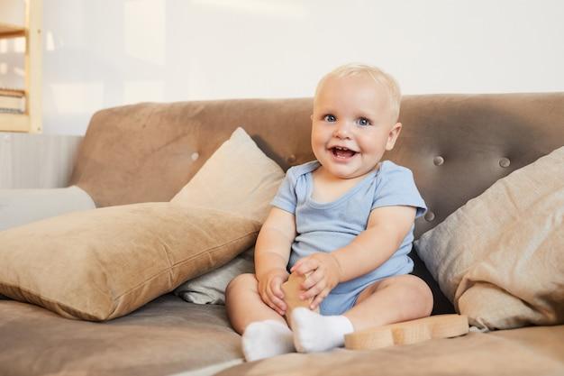 Schuss des niedlichen kleinen jungen, der hellblaue kleidung trägt, die auf lächelndem sofa sitzt