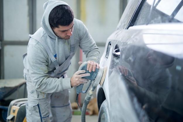 Schuss des professionellen reparaturmanns, der fahrzeug für neuen lack vorbereitet