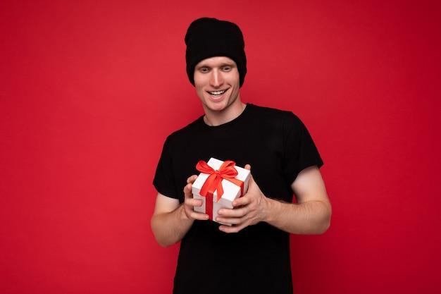 Schuss des schönen glücklichen jungen mannes lokalisiert über der roten hintergrundwand, die schwarzen hut und schwarzes t-shirt hält, das weiße geschenkbox mit rotem band hält und kamera betrachtet.