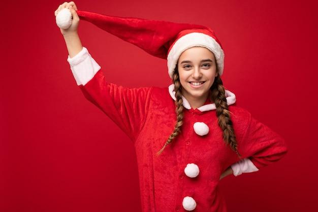 Schuss des schönen glücklichen positiven positiv lächelnden brünetten weiblichen teenagers mit zöpfen, der weihnachtsmannklauselanzug steht, der lokal über roter wand steht