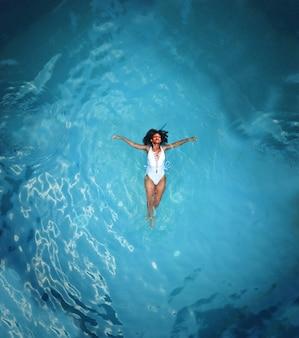 Schuss einer afrikanischen frau im weißen monokini, der auf gewässer schwimmt