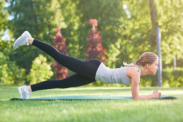 Schuss einer jungen fitnessfrau, die draußen im park arbeitet, die plankenübung tut, die ihr bein im luftgesäß trainiert, trainiert fitness-energiemotivation leichtathletik-aktivitätskonzept.