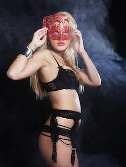 Schuss einer sexy frau in erotischen dessous mit maske