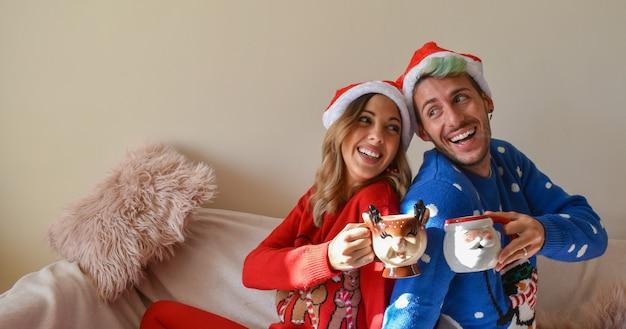 Schuss eines glücklichen paares in den weihnachtshütten und in den kleidern, die lustige tassen halten