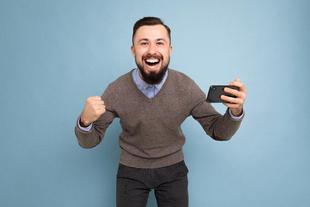 Schuss eines glücklichen überglücklichen gutaussehenden jungen brünetten unrasierten mannes mit bart, der alltägliches grau trägt