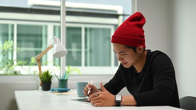 Schuss eines jungen männlichen grafikdesigners, der auf seinem projekt mit digitalem tablett am modernen arbeitsplatz skizziert.
