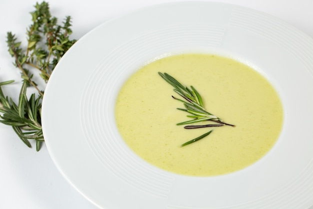 Schuss eines suppentellers mit zucchini-cremesuppe auf einem weißen tisch, der mit grünen pflanzen verziert wird