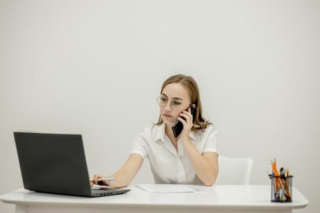 Schuss glückliche geschäftsfrau, die am schreibtisch hinter ihrem laptop sitzt und mit jemandem auf ihrem handy spricht, während sie von zu hause aus arbeitet. heimbüro.