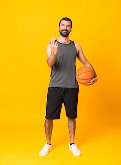 Schuss in voller länge des mannes über dem lokalisierten gelben hintergrund, der basketball spielt und kommende geste tut
